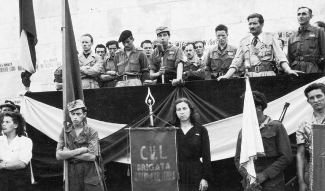 """Schio, maggio 1945: una gran folla si è radunata in piazza Alessandro Rossi davanti al palco delle autorità partigiane. Da sinistra a destra si riconoscono, in primo piano, Orfeo Vangelista """"Aramin"""", vice commissario della Divisione """"Garemi""""; il capitano John Orr-Ewing """"Dardo"""" della missione inglese; Valerio Caroti """"Giulio"""", comandante della Brigata """"Martiri della Valleogra"""", col microfono; Sandro Cogollo """"Randagio"""", commissario della """"Martiri della Valleogra""""; Nello Boscagli """"Alberto"""", comandante della """"Garemi"""". Dietro a Caroti, a sinistra Bruno Redondi """"Brescia"""", comandante del Battaglione """"Apolloni"""" e vice comandante della """"Martiri della Valleogra"""", a destra Elio Busetto """"Guglielmo"""", vice comandante della """"Garemi""""; dietro a Busetto Riccardo Walter, membro del nuovo governo cittadino. Sotto il palco al centro, infine, Anna Costenaro """"Olga"""", la staffetta."""